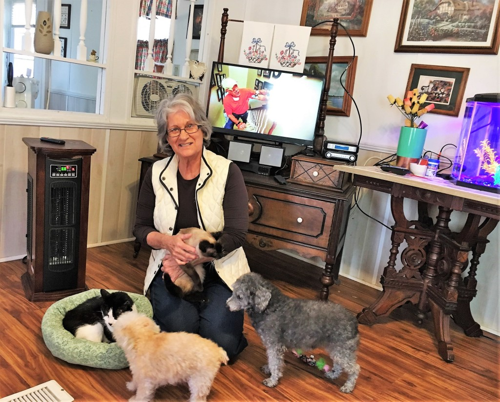 Leah Holt at home with her adopted County Shelter cats Footie and Nutmeg, and dogs Chrissie and BJ.