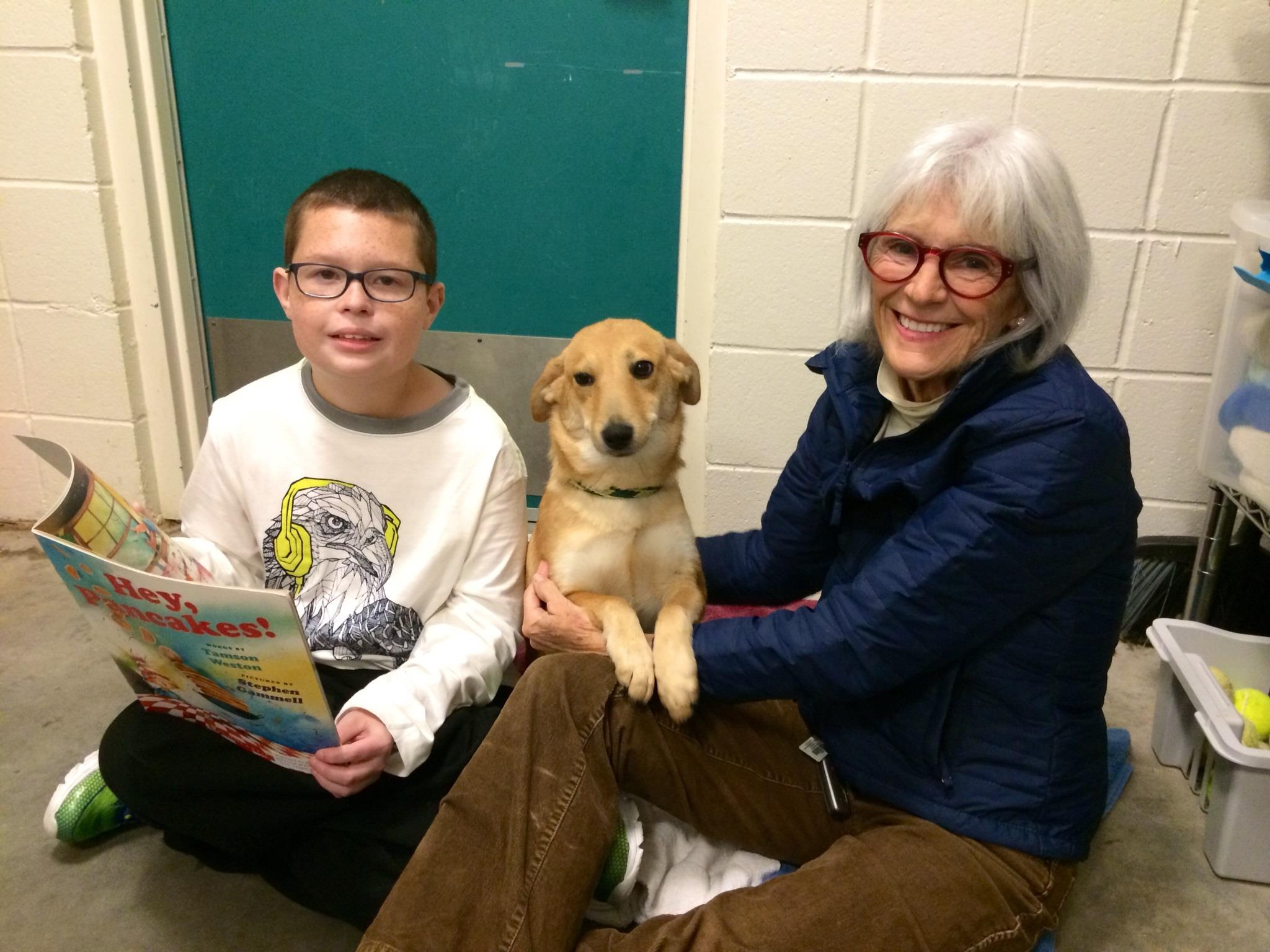 Hope (since adopted) enjoyed a reading session (at the Dog Ears Reading Program) with a young participant and FOTAS volunteer Karen.