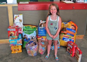 Seven-year-old Marli Cook with the donations her guests brought to her birthday party.