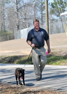 Bobby Arthurs, the chief enforcement officer and ACAS manager, walks a shelter dog.